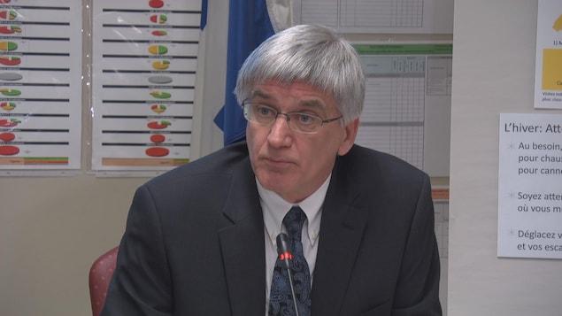 L'homme est assis à une table pendant la conférence de presse.