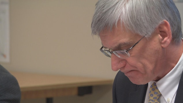 Jean Hébert porte des lunettes et regarde le sol.