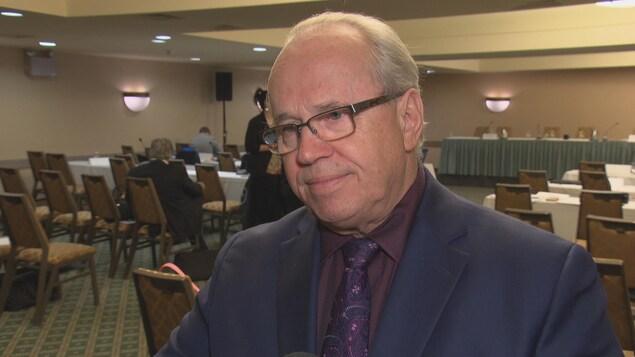 Jean Johnson, dans une salle de réunion, répondant aux questions d'un journaliste.