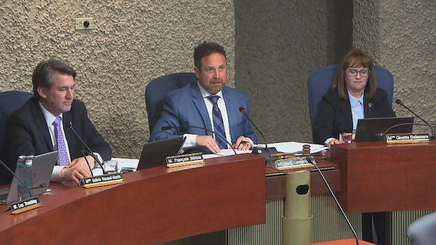 Jean Lamarche aux côtés de Ginette Bellemare et François Bélisle dans la salle du conseil municipal à l'hôtel de ville de Trois-Rivières.