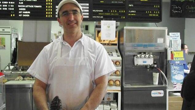 Jean LeBlanc derrière le comptoir de son commerce, un corner de crème glacée au chocolat dans la main.