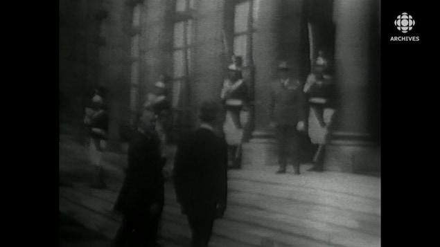 Jean Lesage montant les marches de l'Élysée devant la garde française.
