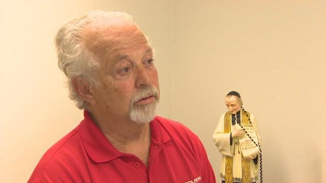 Un homme aux cheveux blancs porte un polo rouge.