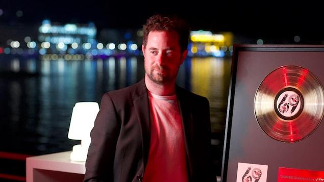 Le pianiste Jean-Michel Blais recevant son disque d'or sur la plage devant le palais des Festivals, à Cannes.