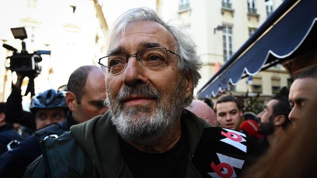 Jean-Paul Dubois, entouré de micros, dans une foule.