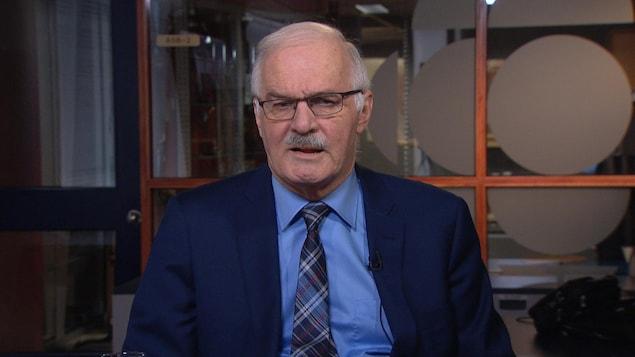 Un homme, qui porte des lunettes rectangulaires et qui est vêtu d'un veston, d'une blouse et d'une cravate, parle en regardant directement la caméra. Il a les cheveux gris et une petite moustache.