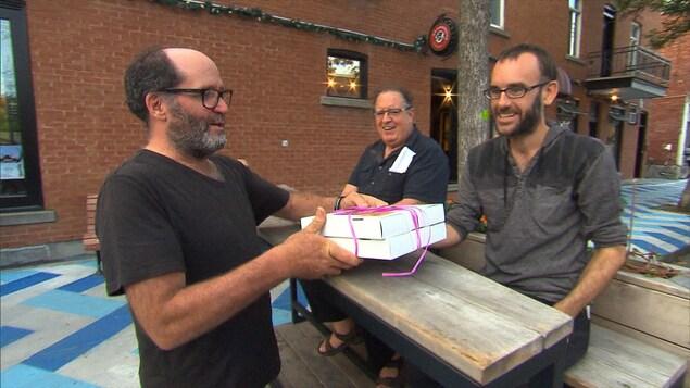Jean-René Bernier offre un paquet à un autre homme.