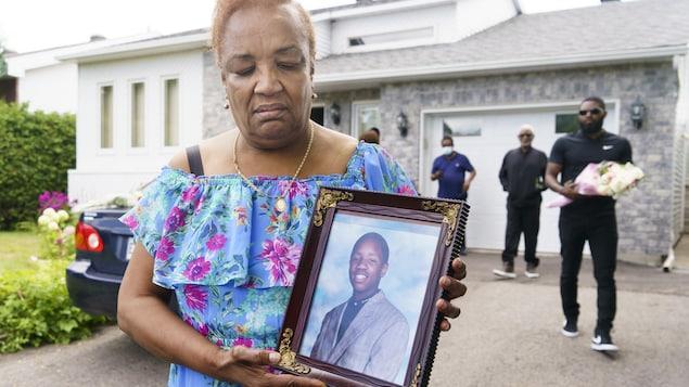 La mère tient un cadre dans lequel se trouve une photo de son fils.