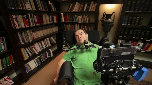 Jean Truchon dans un fauteuil roulant lors d'une conférence de presse dans une bibliothèque.