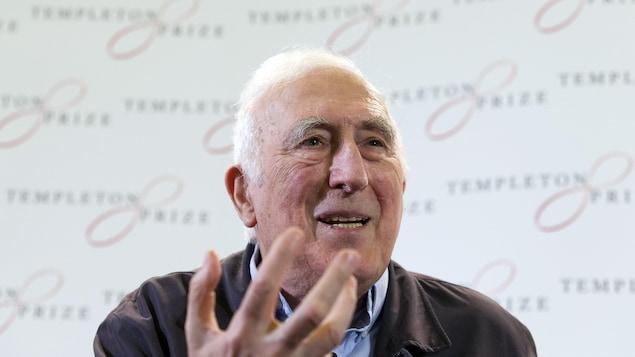 Jean Vanier sourit en discutant avec les journalistes.