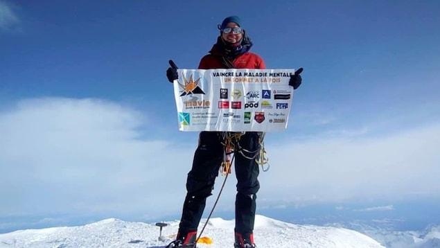 Jean-François Dupras tient dans ses mains, en haut du sommet, sa bannière: Vaincre la maladie mentale, un sommet à la fois.