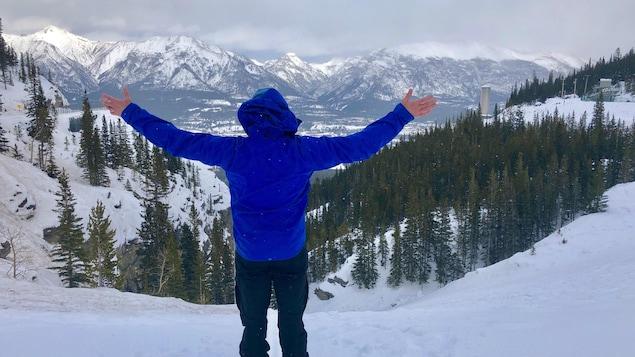 Un homme se tient debout dos à la caméra et face aux montagnes avec les bras en l'air.
