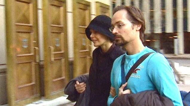 Jennifer Clark porte un manteau et un chapeau noir. Jeromie porte des lunettes et un chandail bleu. Ils se rendent à leur procès.