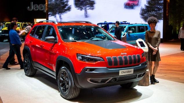 Un véhicule Jeep Cherokee exposé dans un salon de l'auto. Une femme se tient près du véhicule.