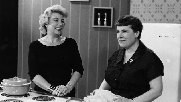 Dans un studio de télévision, debout à un comptoir, l'animatrice discute avec Jehane Benoît qui prépare un poulet.