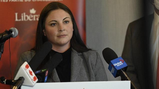 Une femme au micro, lors d'une conférence de presse