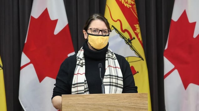 Jennifer Russell en conférence de presse, au lutrin devant des drapeaux du Nouveau-Brunswick.