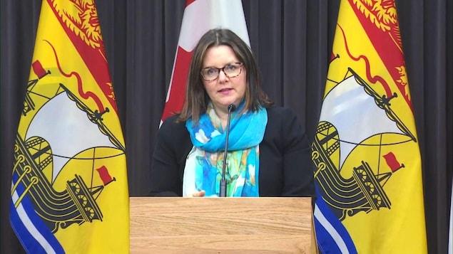 Jennifer Russell au micro, entre des drapeaux du Nouveau-Brunswick.