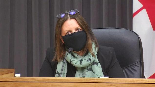 Jennifer Russell, le visage couvert d'un masque et ses lunettes sur la tête, est assise lors d'une conférence de presse.