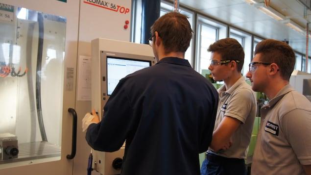 On voit deux apprentis, dont Jérémie, de profil, qui observent leur formateur en train de manipuler un équipement électronique dans l'usine. Ils portent des lunettes protectrices et l'uniforme de l'entreprise.
