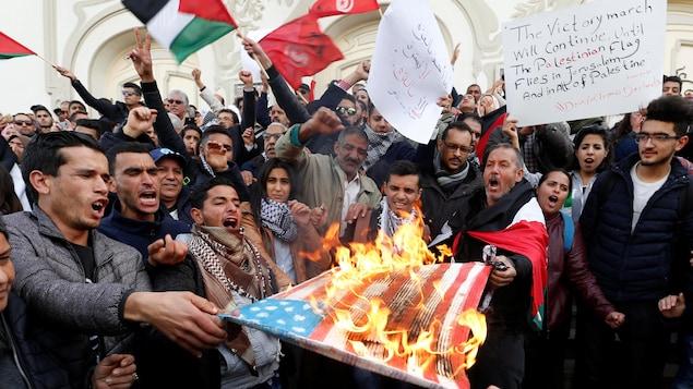 Des manifestants brûlent un drapeau des États-Unis.
