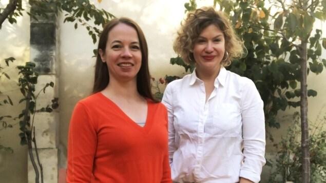 Les deux femmes posent côte à côte et sourient en regardant l'objectif.