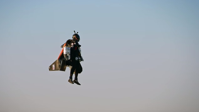 Un homme portant une combinaison spéciale est en suspension dans les airs.