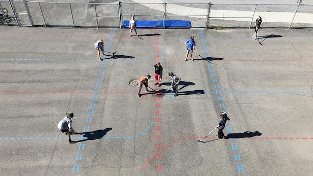 Plan aérien de jeunes qui pratiquent le hockey-balle dans une cour d'école.