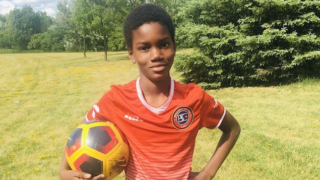 Karim est debout sur l'herbe d'un parc, un ballon de soccer sous le bras. Il sourit à la caméra et porte un maillot de joueur de soccer au logo du Brampton Soccer Centre.