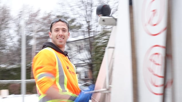 Un jeune homme vêtu d'orange est accroché à un camion.