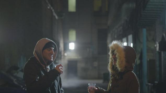 On voit deux jeunes personnes dans une ruelle, le soir, en train de consommer une boisson dans des verres en plastique.