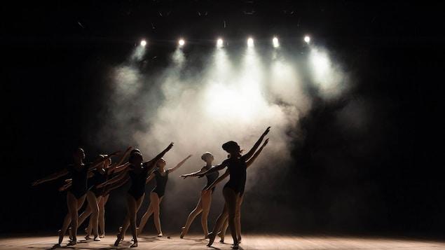 Des jeunes pratiquent le ballet sur une scène enfumée.