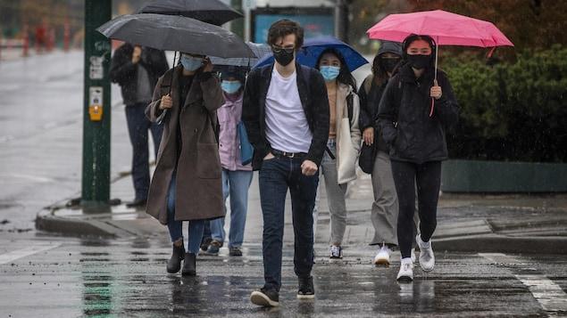 traversent une rue pendant une averse, le 15 octobre 2021 à Vancouver.BC 省10 月 25 日起对完全接种疫苗者放开