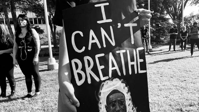 """Un manifestant tient une affiche indiquant : """"I can't breathe"""" (« Je ne peux pas respirer »)"""