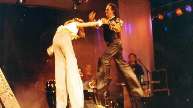 Un homme sur échasses tient par la main sa partenaire de scène, également sur des échasses, alors que des musiciens derrière eux les observent.
