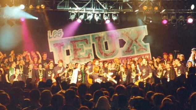 Une foule de jeunes participants sur scène devant une foule nombreuse dans la salle. Au fond de la scène, on peut lire Les Jeux.