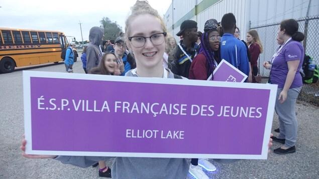 Une fille tient une pancarte elle sourit