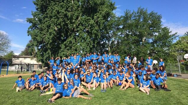 Des jeunes posent dans leur tenue de sport bleue.