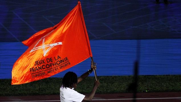 Ruth Marie Christelle Gbagbi, athlète de la Côte d'Ivoire en taekwondo, défile avec un drapeau des Jeux de la Francophonie.
