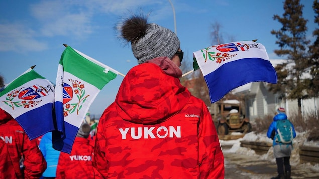 Un athlète porte un manteau aux  couleurs du Yukon lors d'une parade à Whitehorse en mars 2020.