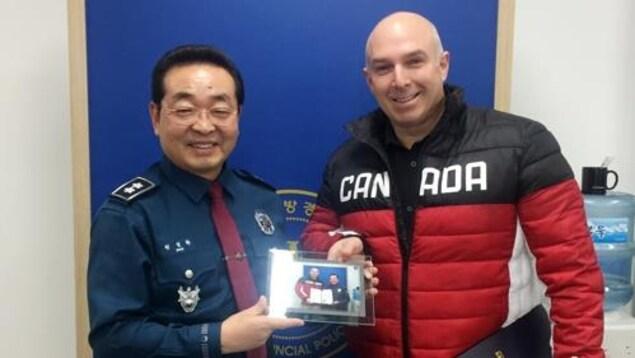 Un homme asiatique en uniforme de policier remet une photo encadrée à un homme blanc qui porte un manteau d'hiver avec la mention Canada. Tous les deux sourient pour la caméra.