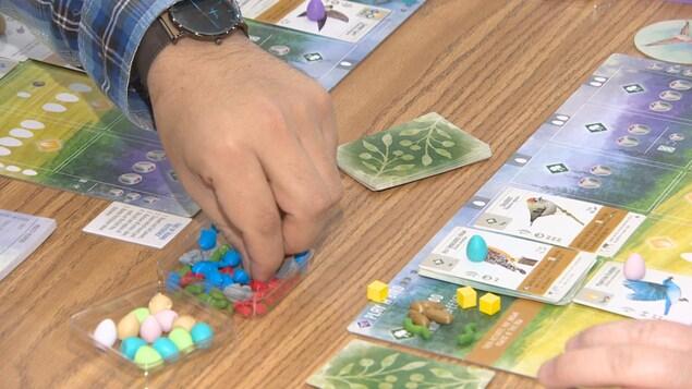 La main d'un joueur pioche un jeton dans une petite boîte en plastique faisant partie d'un jeu de société.