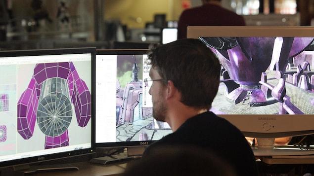 Un concepteur de jeux vidéo en train de travailler à l'ordinateur.