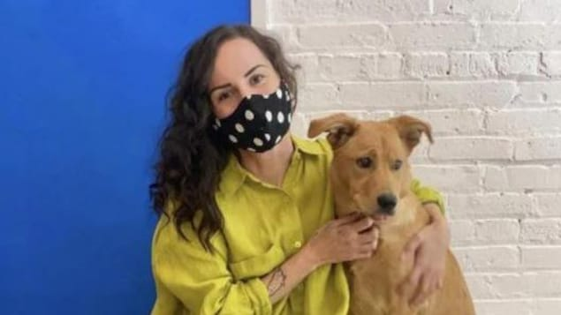 Jilian Zdunich porte un masque et une blouse jaune. Elle est photographiée avec son chien.