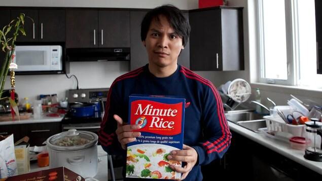 May hawak na kahon ng Minute Rice si Jim Agapito sa loob ng kusina.