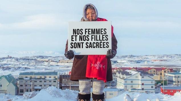 Une femme tient une affiche où l'on peut lire «nos femmes et nos filles sont sacrées».