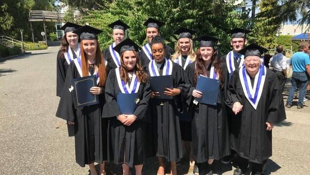 Joan Deebank tient la main de sa camarade de classe alors qu'elle et 10 étudiants de l'école posent ensemble habillés en toge.