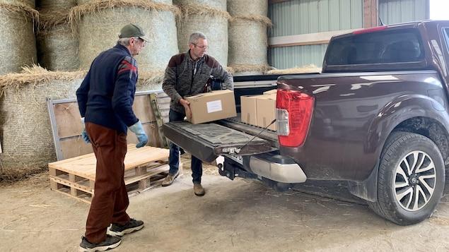 Deux hommes chargent des boîtes dans une camionnette.