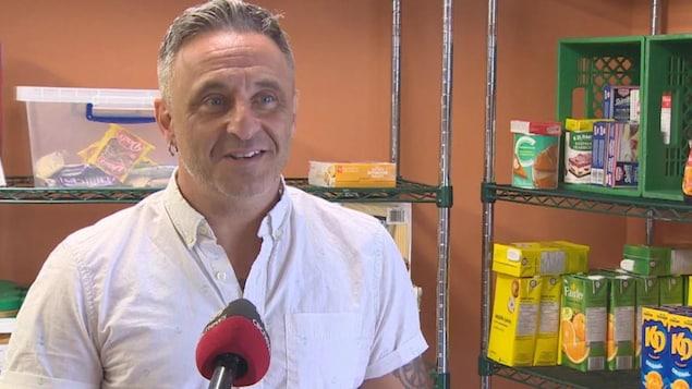 Un homme souriant près d'étagères où sont déposés quelques paquets et boîtes d'aliments.