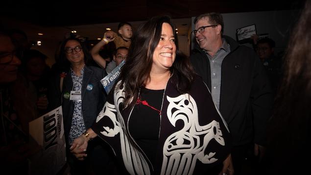 Une femme souriante avec une veste noire et des motifs autochtones de couleur blanche déambule parmi des militants heureux.